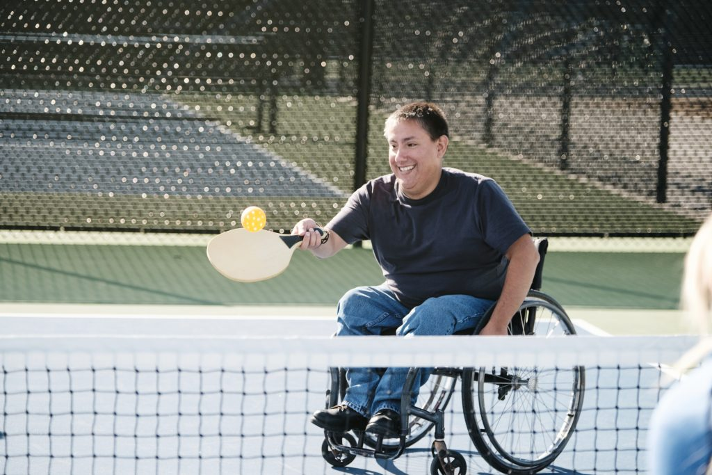 A young man in a wheelchair playing the game of pickleball on a court.
